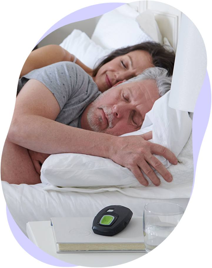 A couple sleeps soundly with the Inspire remote on their nightstand