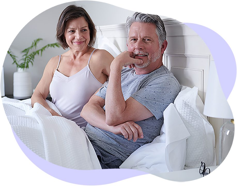 A happy well-rested couple sits in their bed
